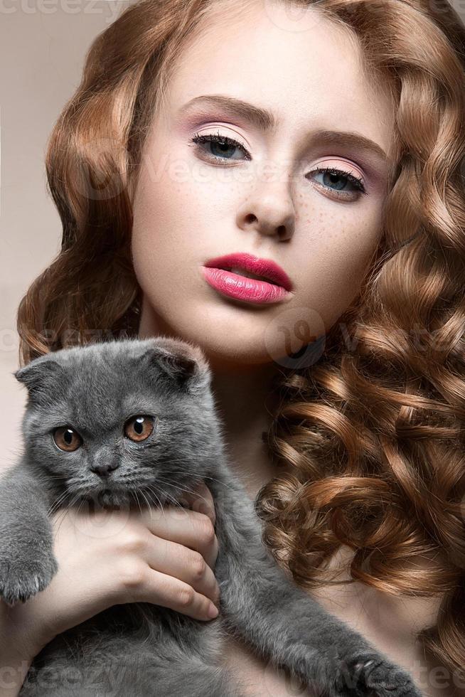 vacker ung flicka, naturlig ljus makeup och lockar med en foto