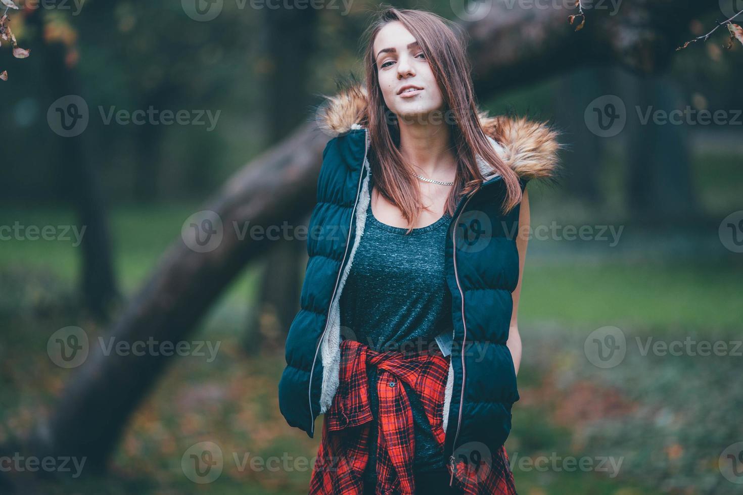 ung vacker flicka som står nära trädet. foto