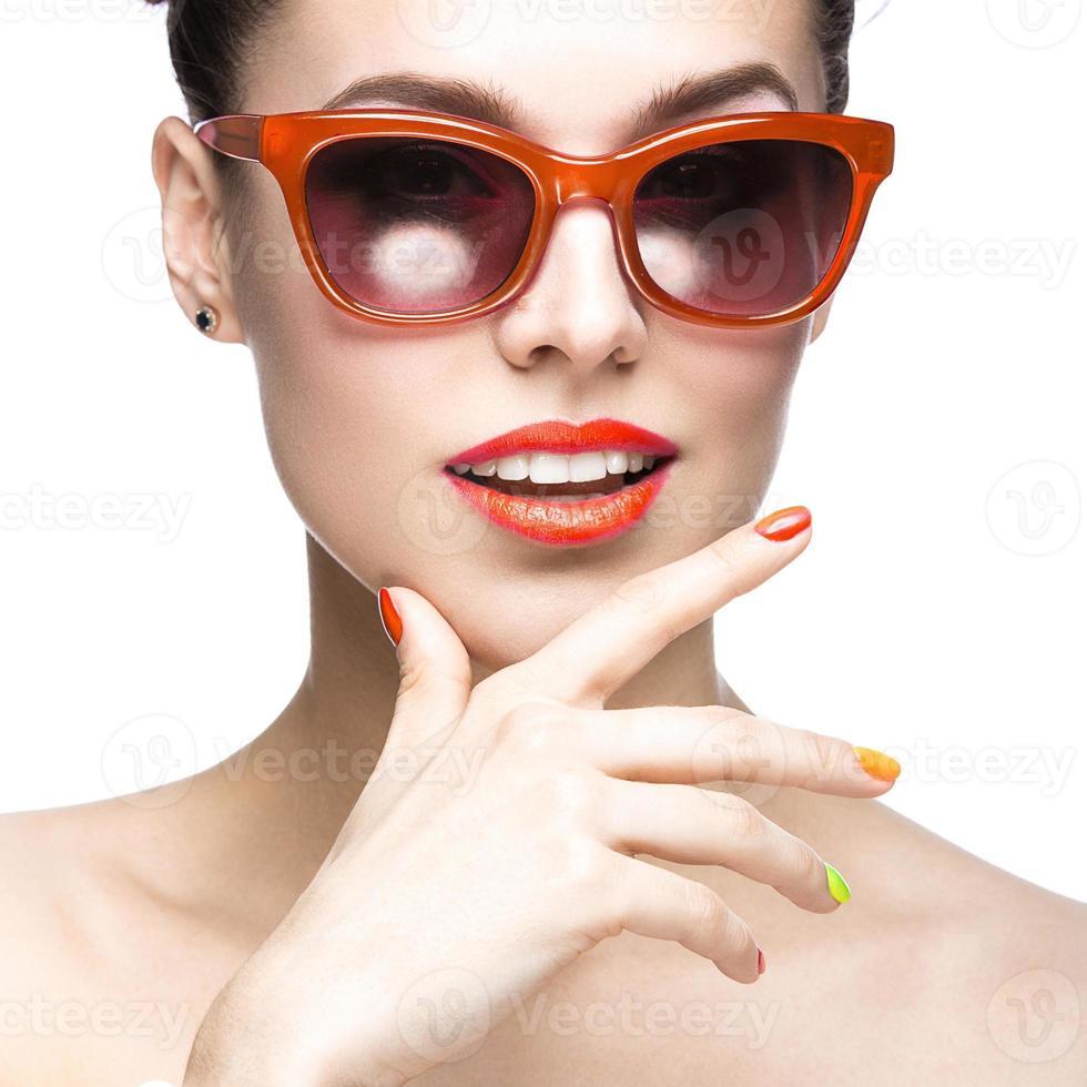 en flicka som bär röda solglasögon och färgglada naglar foto