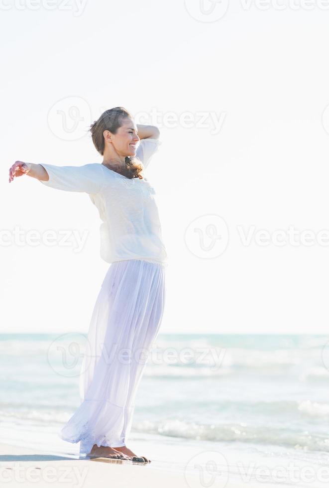 glad ung kvinna kopplar av vid havet foto