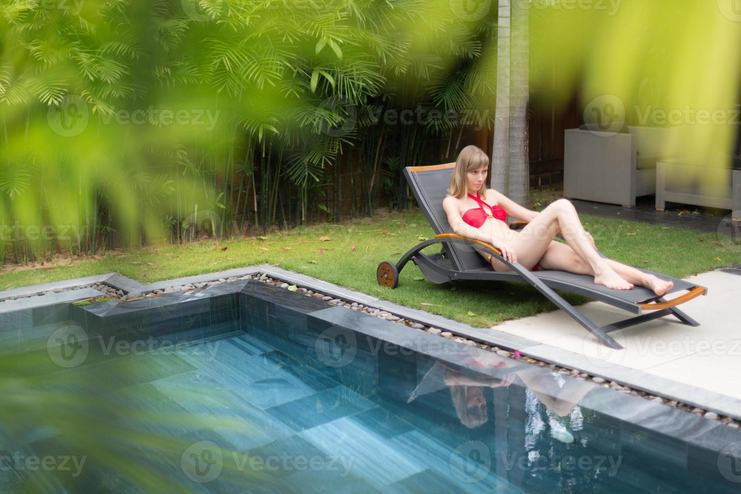 kvinna avkopplande på schäslong nära poolen. foto