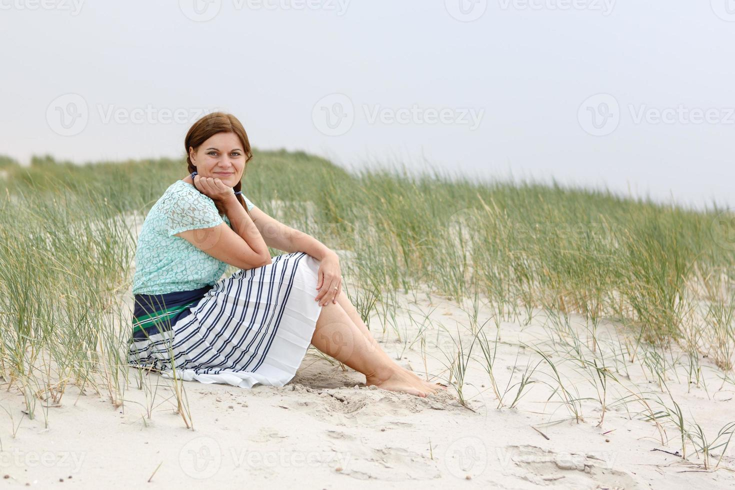 ung glad tjej kopplar av på sanddyner foto