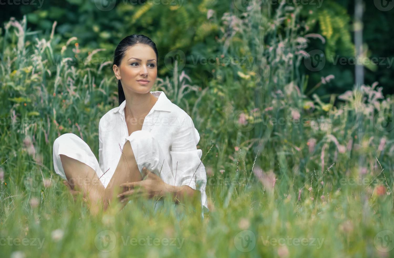 ung avkopplande kvinna som sitter på gräset foto