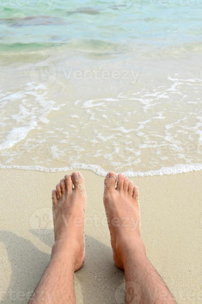 man bara fötter kopplar av på stranden. foto