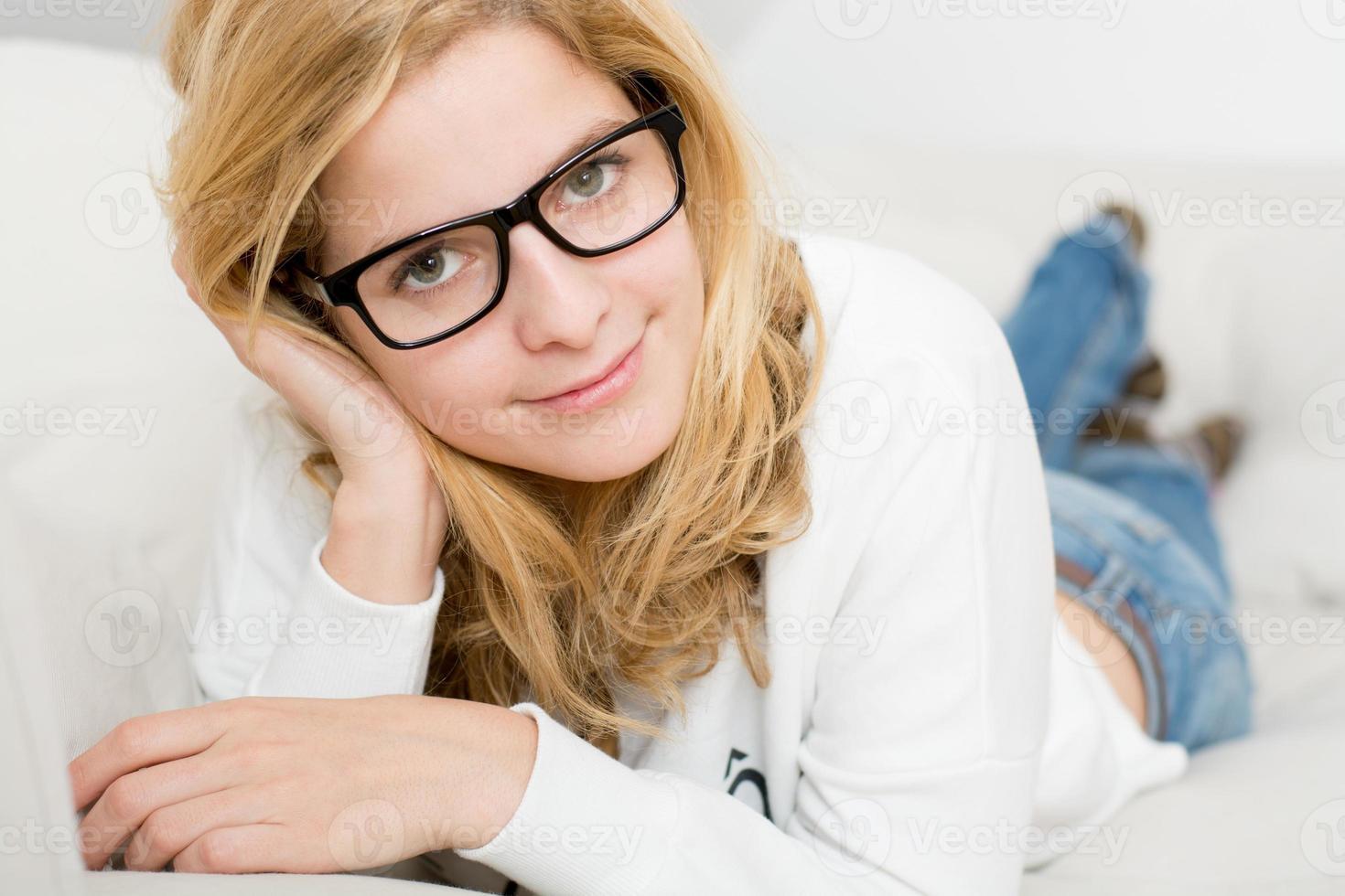 ung vacker kvinna som kopplar av på soffan hemma foto