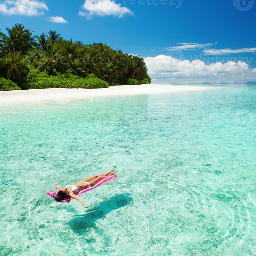 kvinna avkopplande på uppblåsbar madrass i havet foto