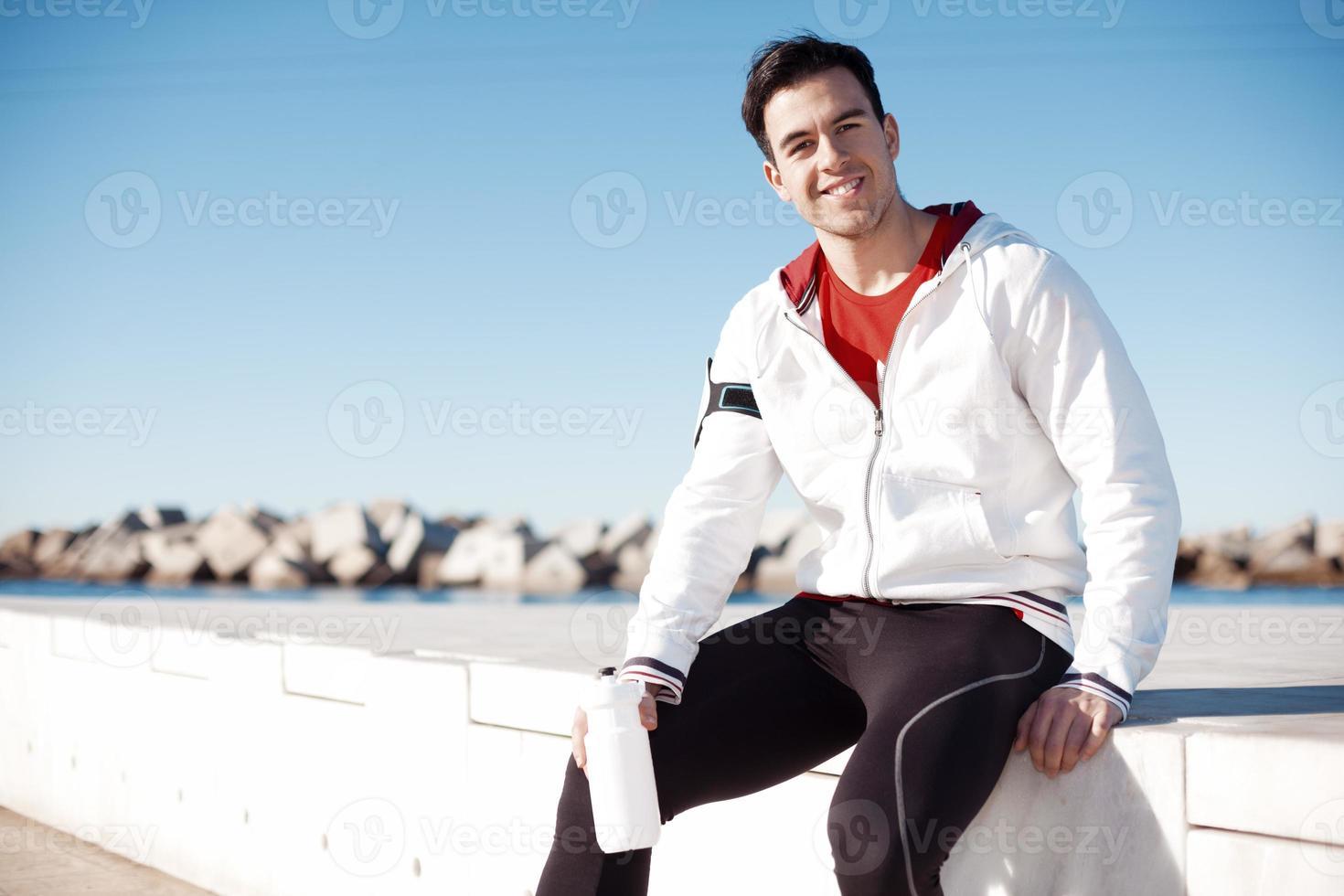 idrottsman med en flaska vatten avkopplande efter träning foto