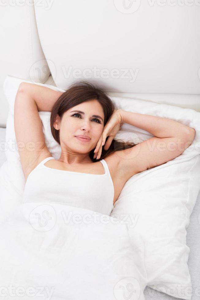 ung kvinna kopplar av i sängen foto