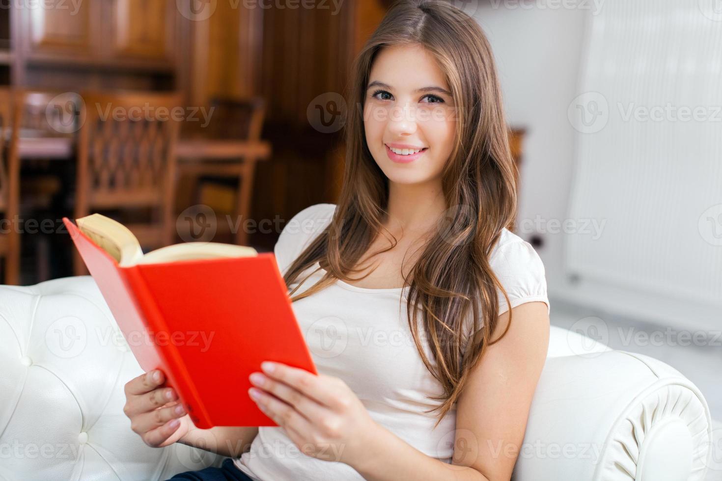 kvinna som läser en bok medan du kopplar av i soffan foto