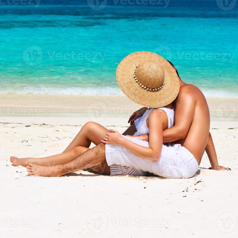 par i vitt kopplar av på en strand vid Maldiverna foto