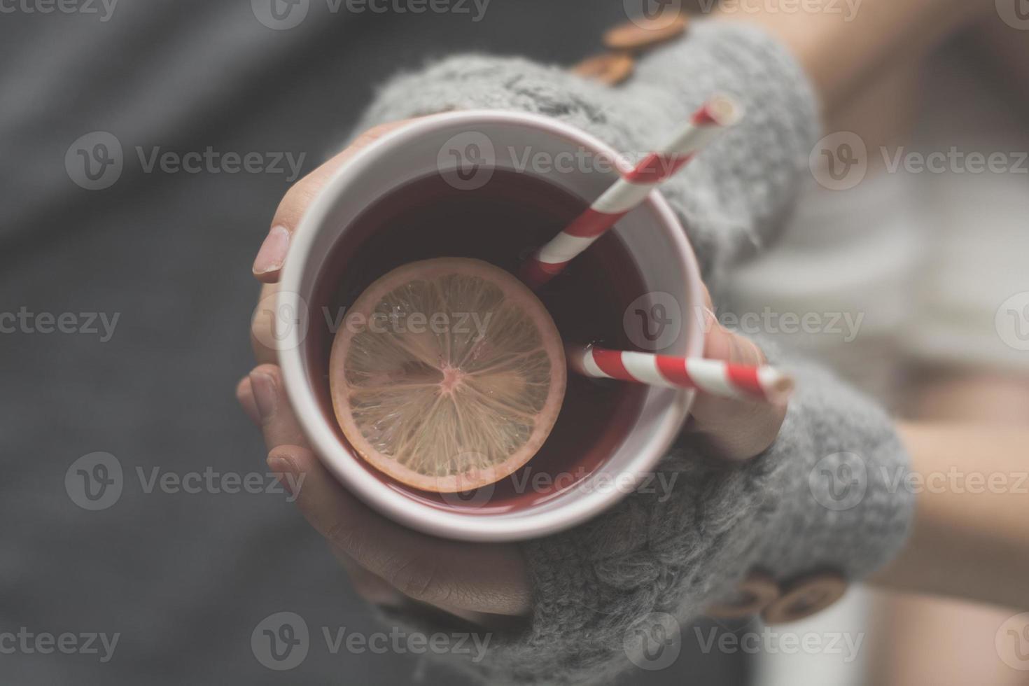 ung kvinna kopplar av i sängen med en kopp te foto