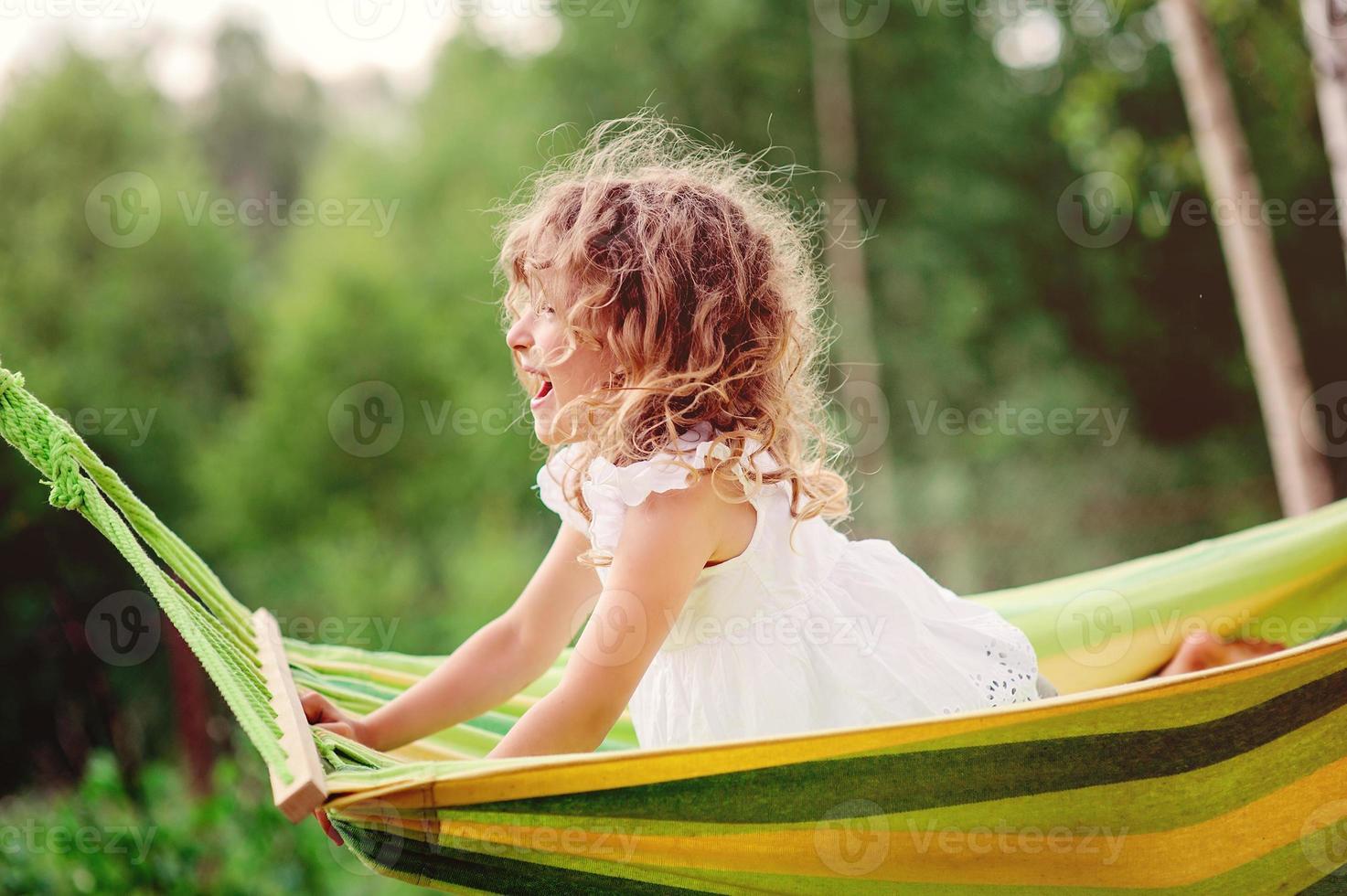 glad barnflicka som kopplar av i hängmatta i sommarträdgård foto