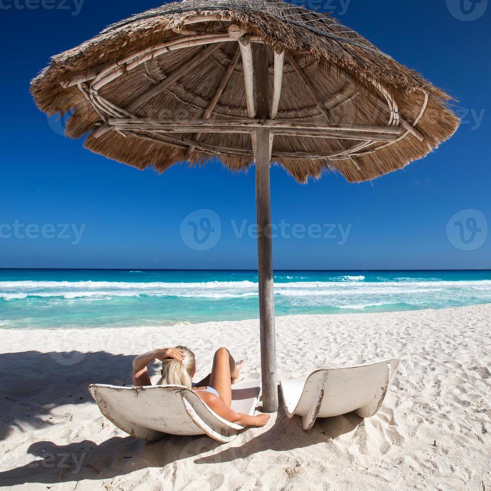 kvinna avkopplande på den karibiska stranden med parasoller och sängar foto