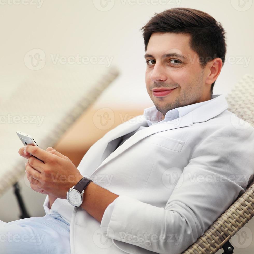 glad avslappnad brudgum i vit kostym som sitter nära bänken på foto