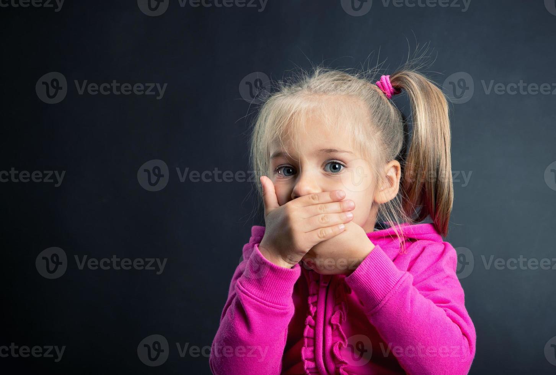 liten flicka täcker munnen med händerna foto
