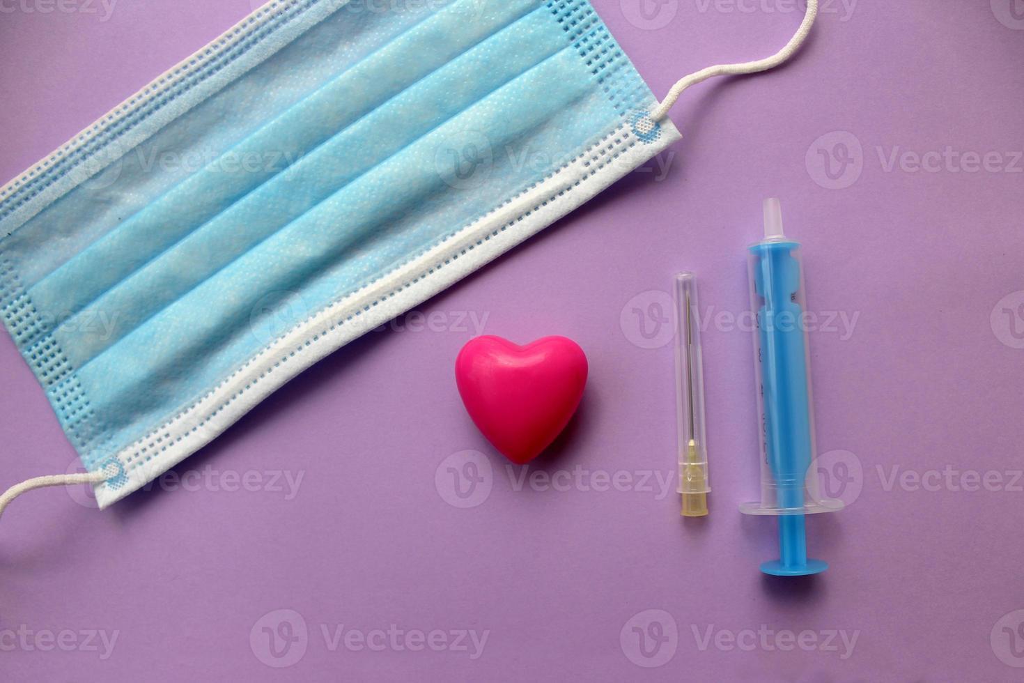 skyddande kirurgisk mask, spruta och nål foto