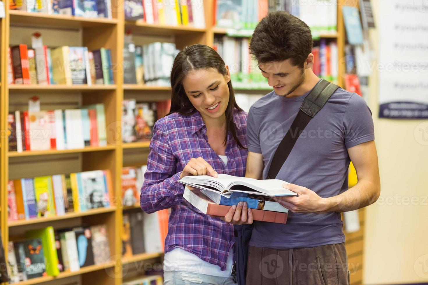 leende vänner student läser läroboken foto
