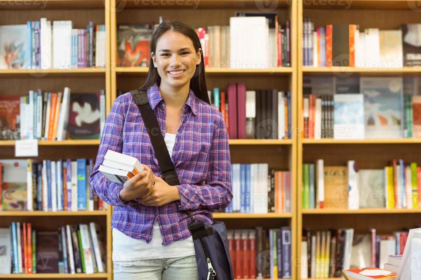 leende universitetsstudent som håller läroboken foto