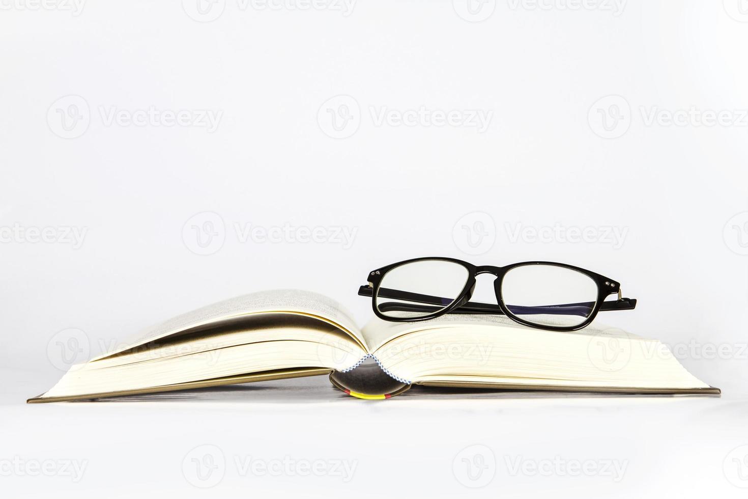 svarta rimmade glasögon placerade på öppnad bok foto