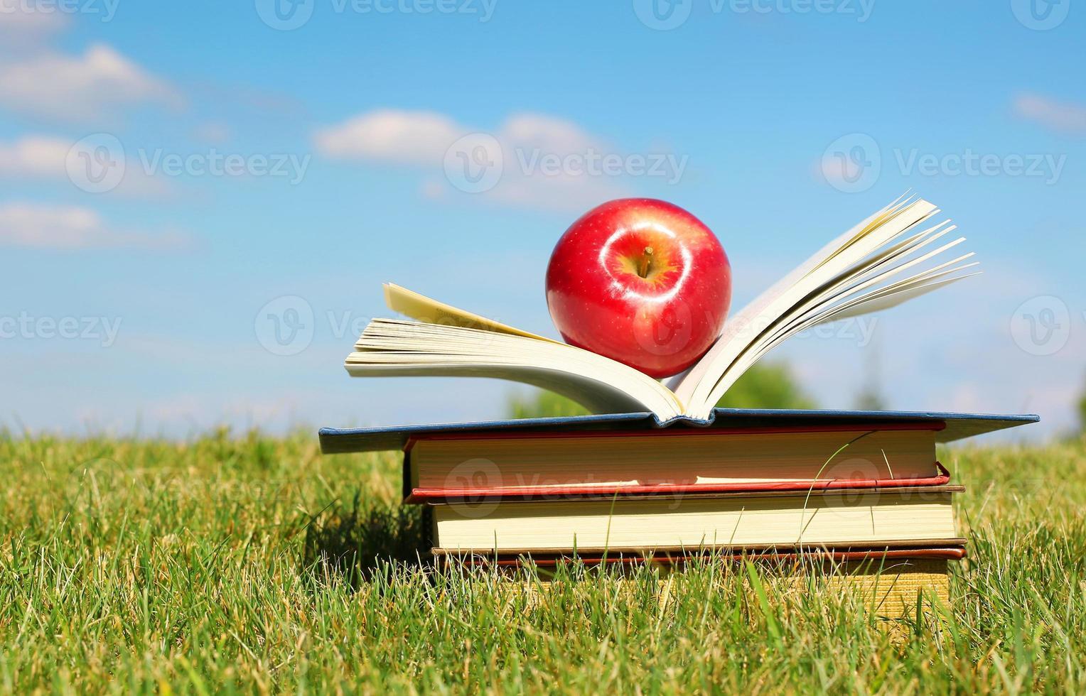 tillbaka till skolan. öppen bok och äpple på gräs foto