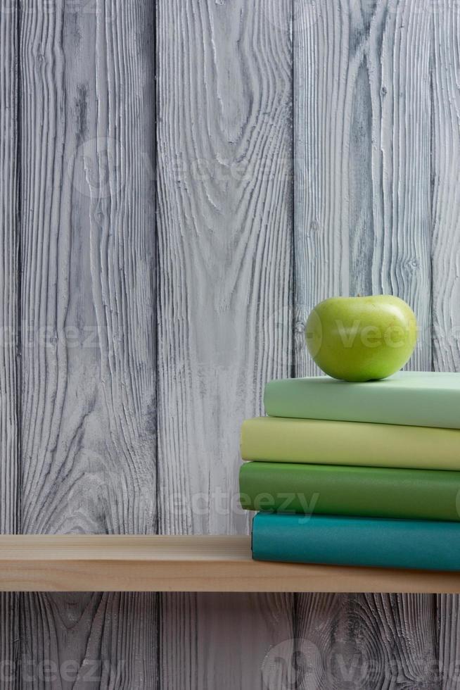 bunt med färgglada böcker och grönt äpple. tillbaka till skolan foto