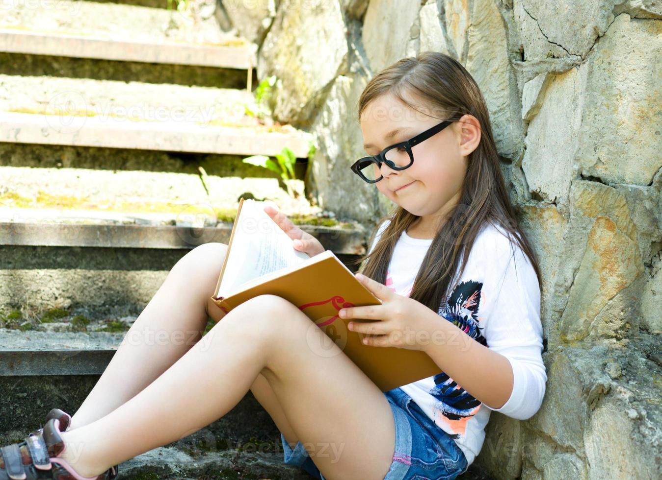 liten flicka läser en bok utomhus foto