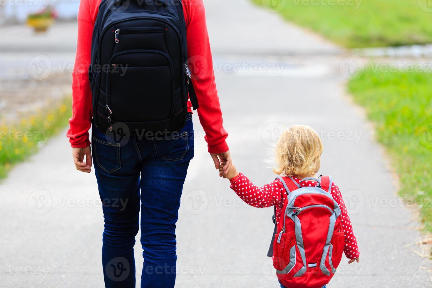 mamma som rymmer handen av lilla dotter med ryggsäck utomhus foto