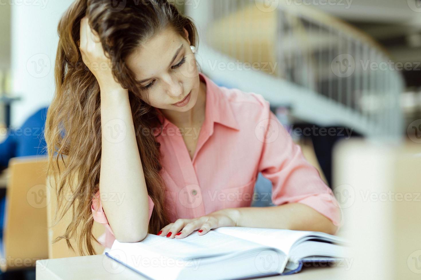 vacker kvinna studerar i biblioteket foto
