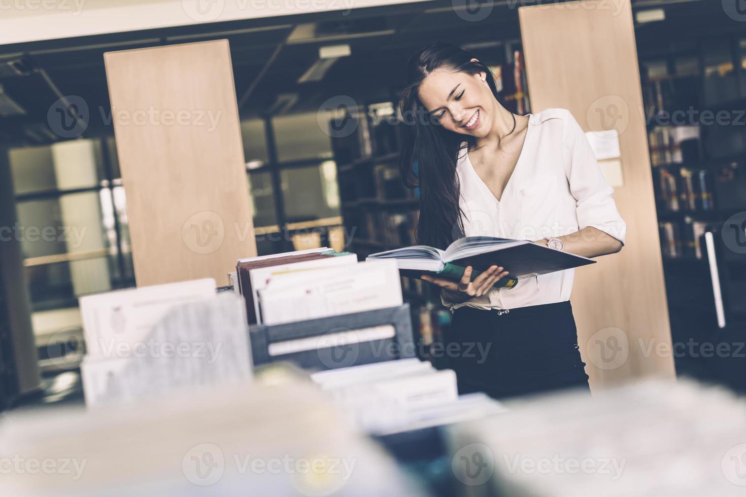 vacker kvinna läser böcker i ett bibliotek foto