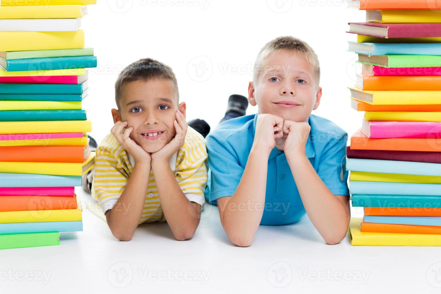 studenter som sitter bakom hög med böcker på vit bakgrund foto
