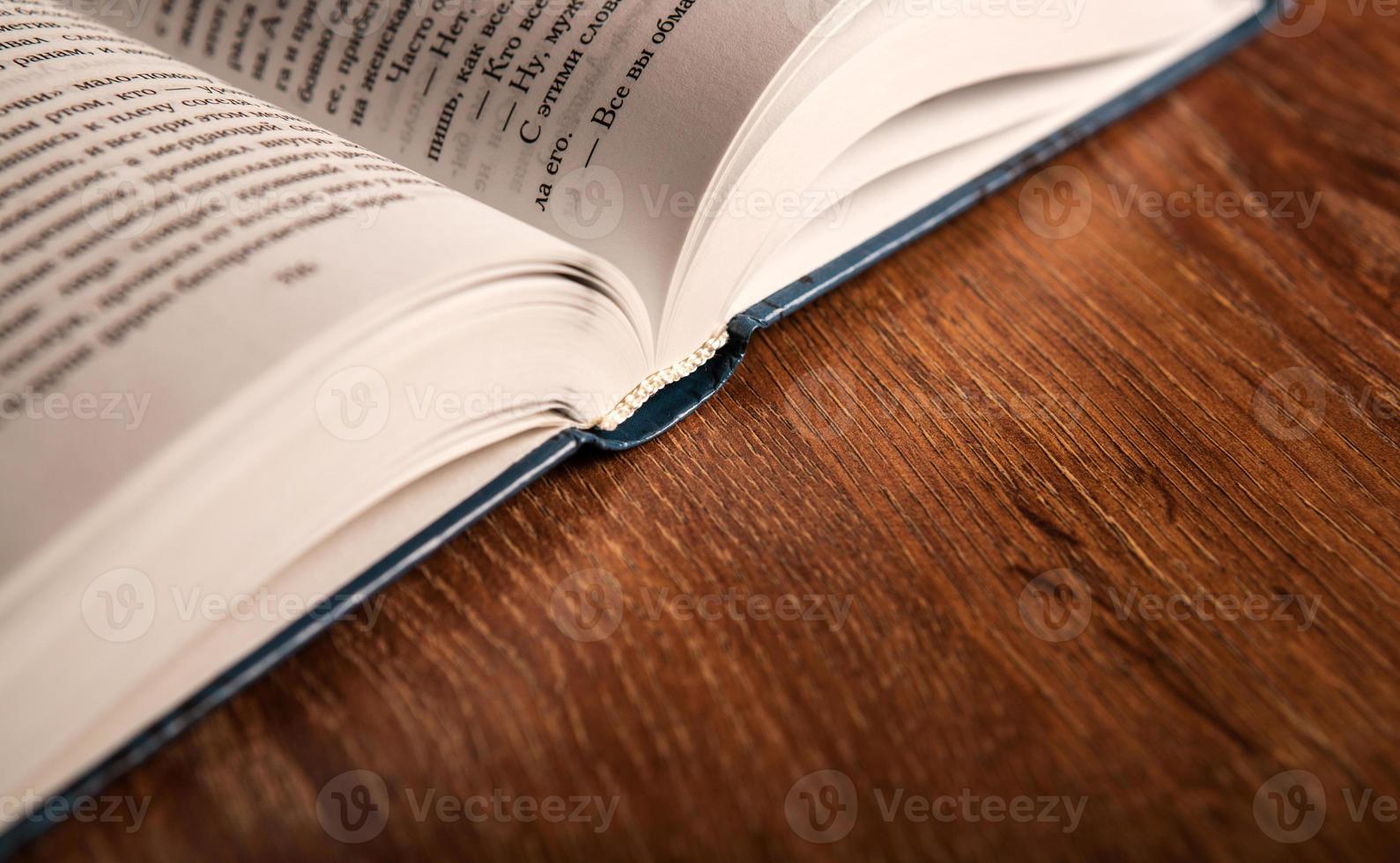 öppna stor bok på ett träbord foto