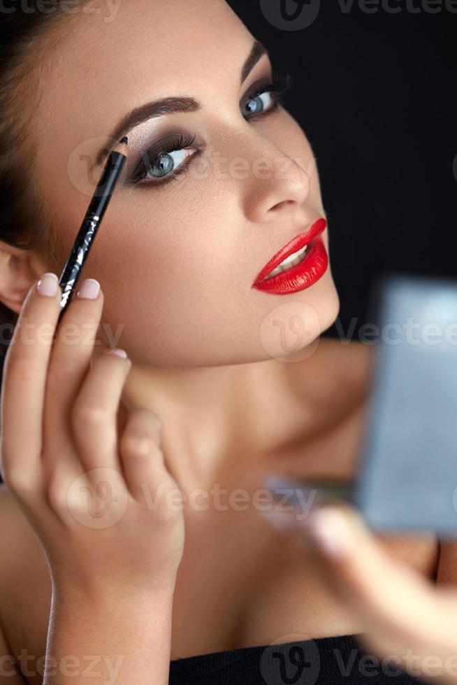 smink. vacker kvinna gör smink. ögonbrynspenna. röda läppar foto