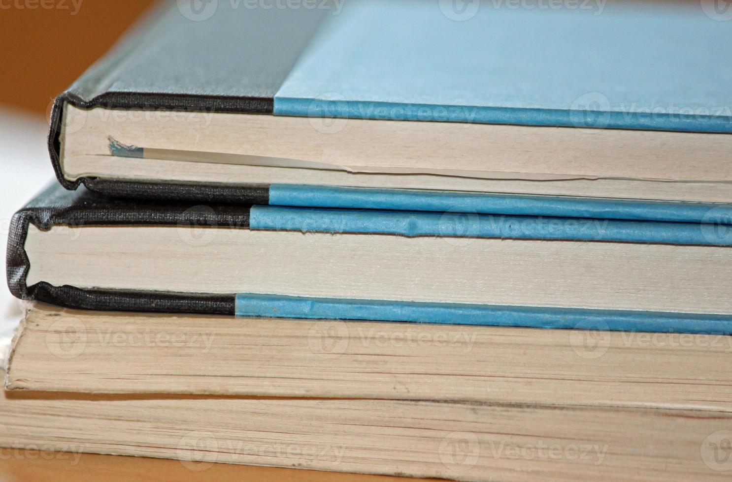 närbild av en bunt böcker på ett skrivbord foto