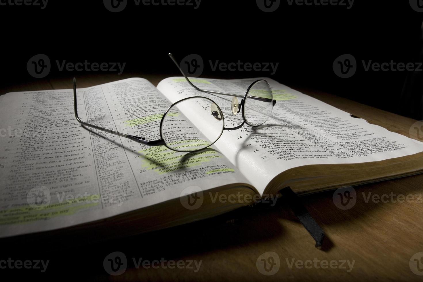 glasögon på öppen bibel foto