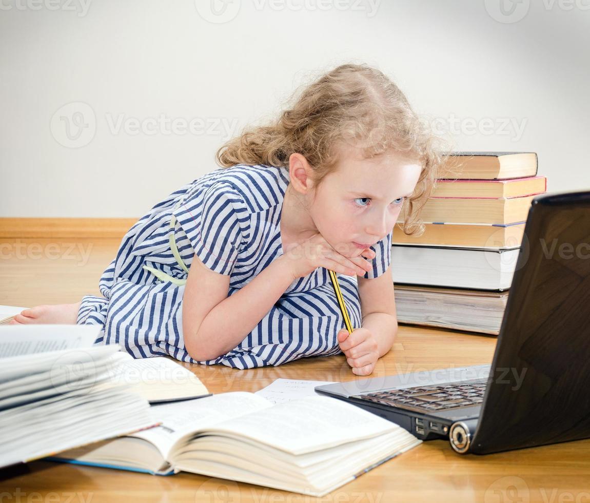 smart liten flicka skriver examen hemma. foto