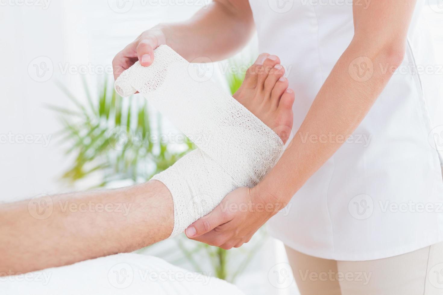 läkare bandager hennes patientens fotled foto