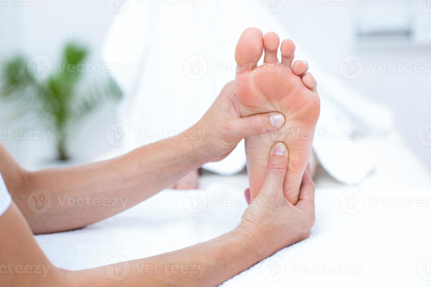 fysioterapeut som gör fotmassage foto