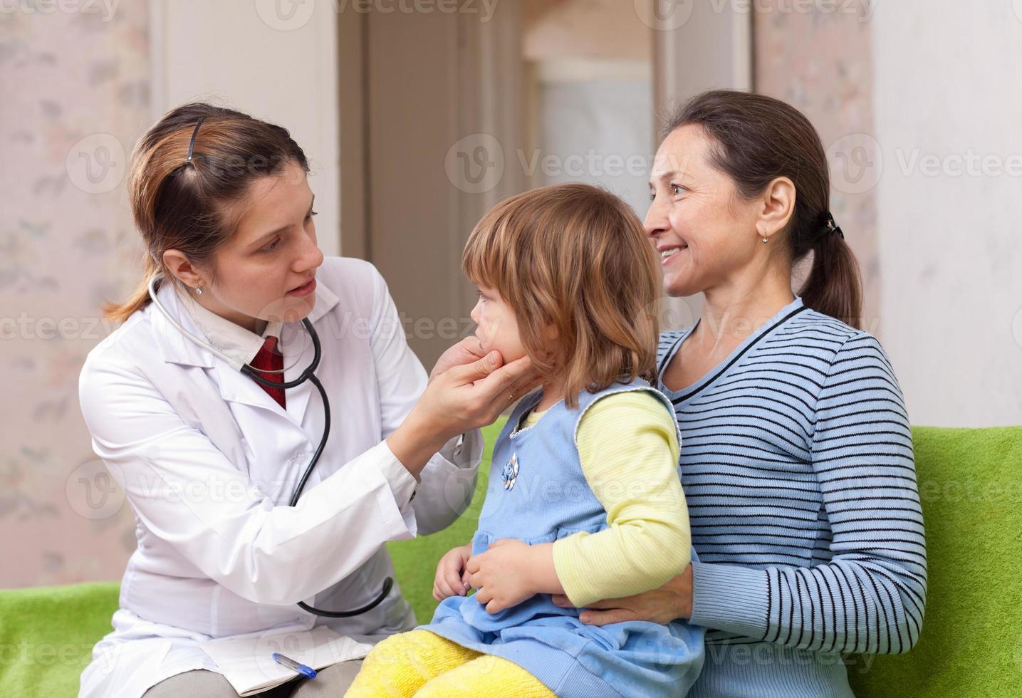 barnläkare som undersöker barn foto