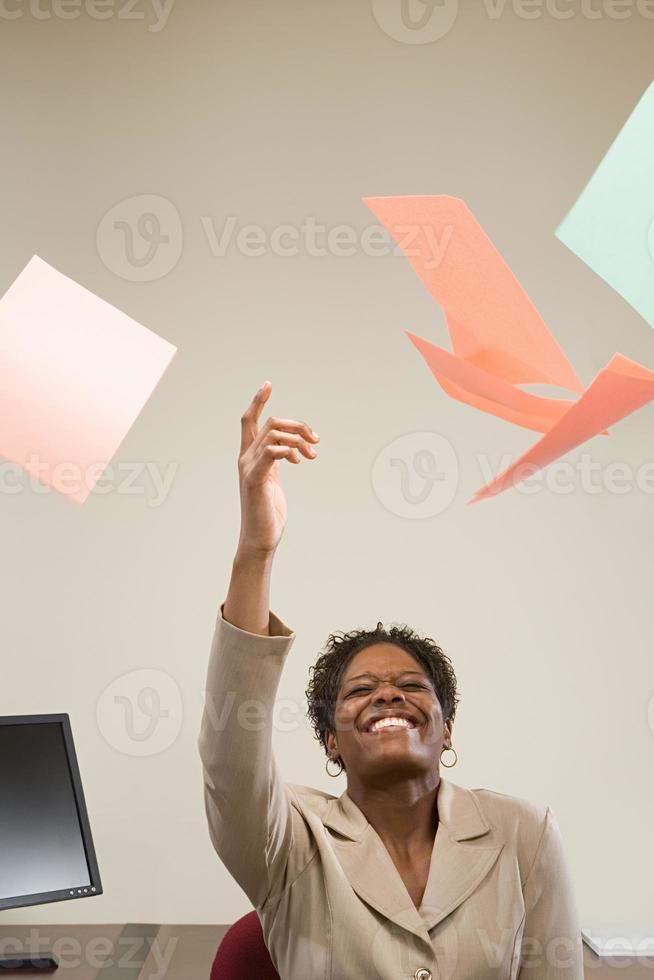 kvinna som kastar papper i luften foto