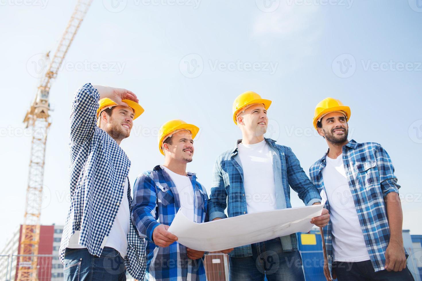 grupp byggare med surfplatta och ritning foto