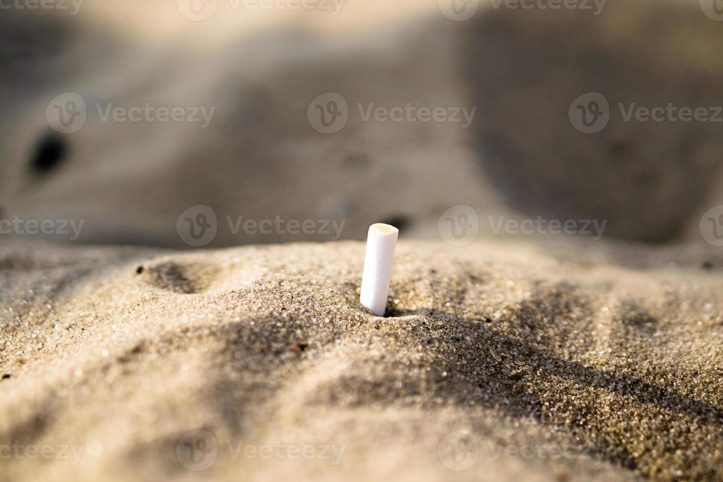 rökt cigarett i sandbakgrundens makrobakgrund foto