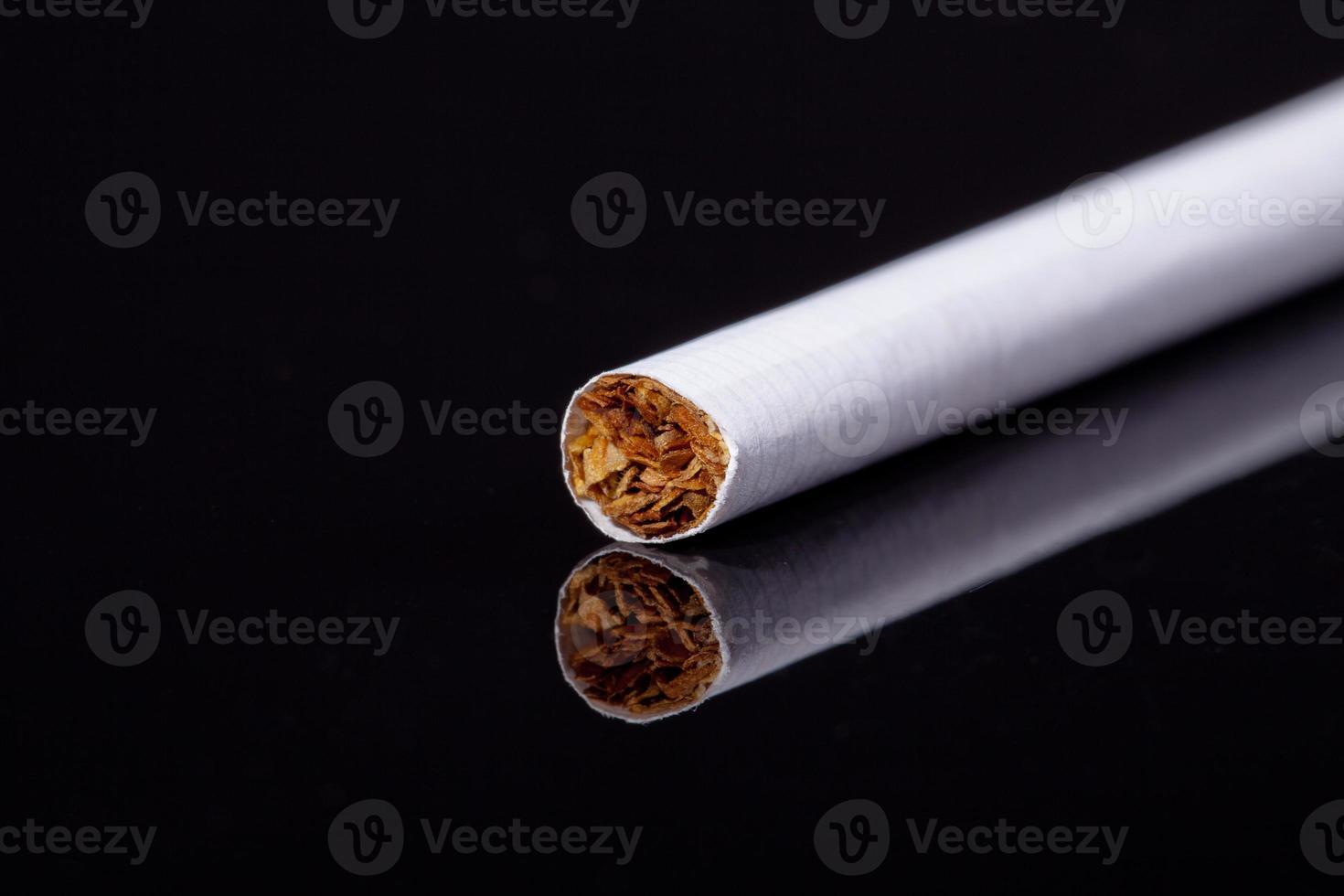 enda tunn cigarett isolerad på svart bakgrundsmakro foto