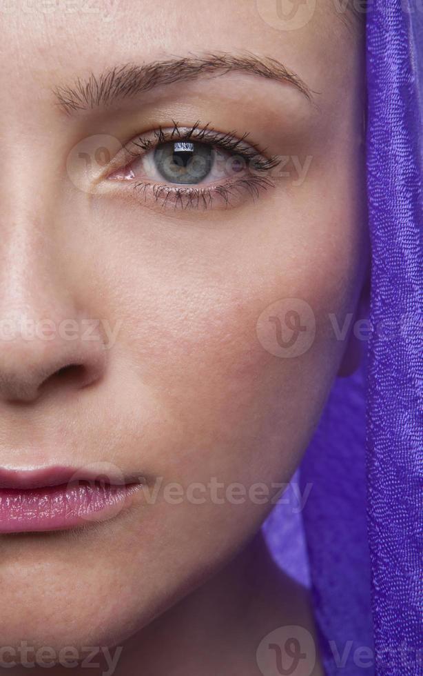 halv ansikte av ung vuxen flicka med lila foulard foto