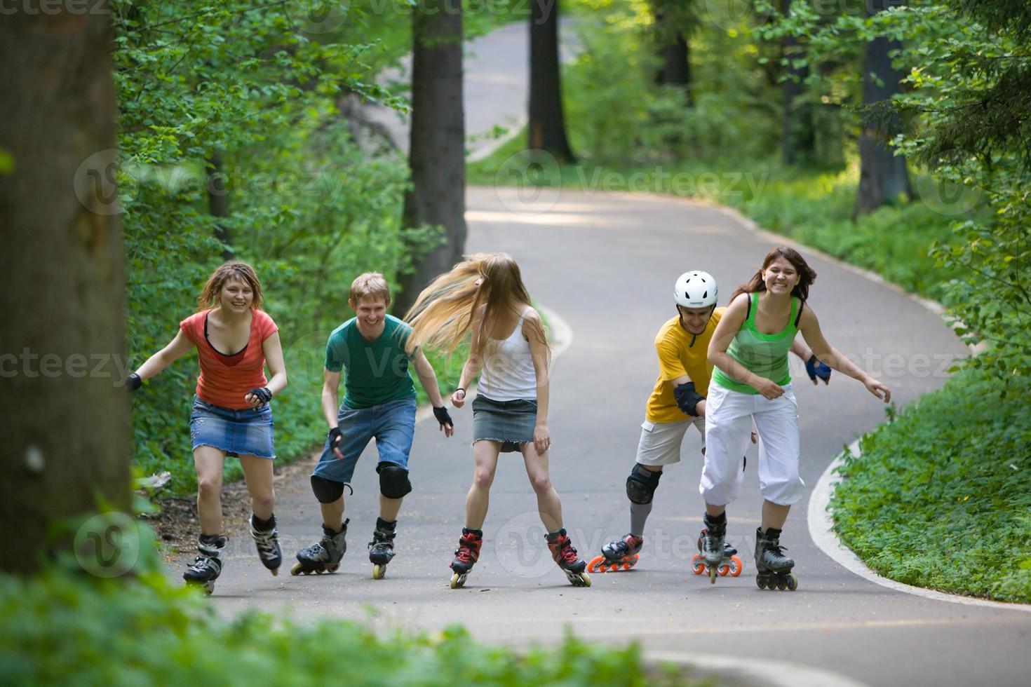 grupp tonåringar som rullar på väg i en park foto