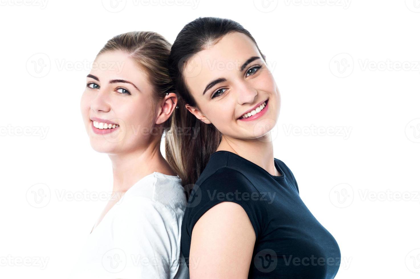 glada tonåriga flickor som står rygg mot rygg foto