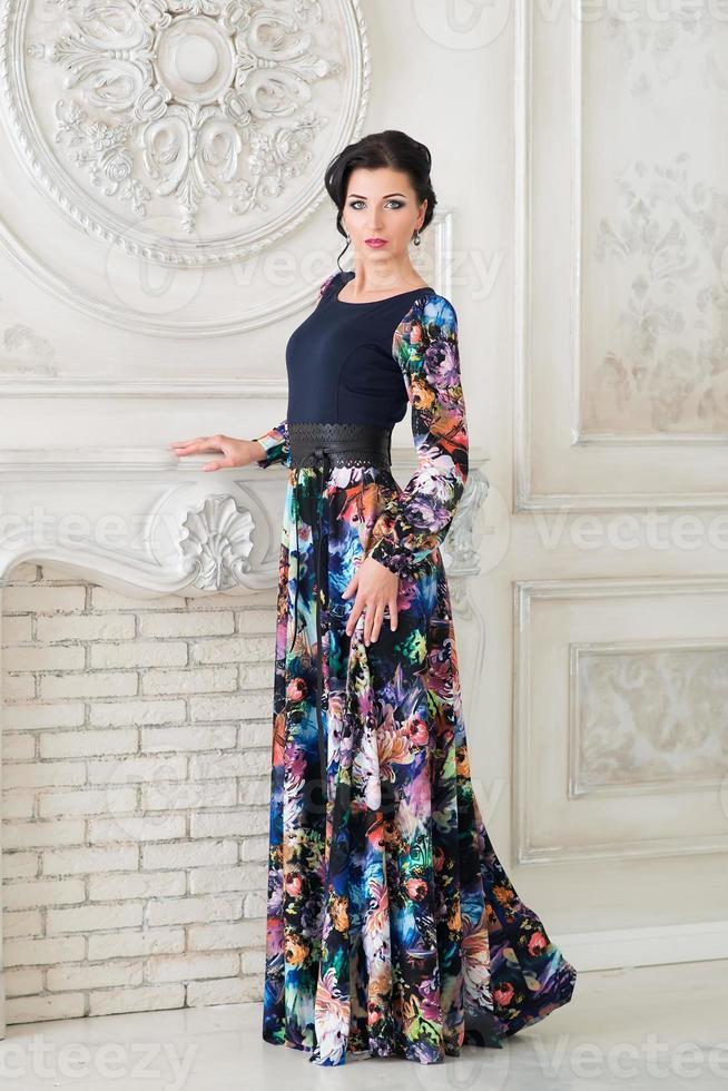 kvinna i lång attraktiv färgglad klänning i interiör foto