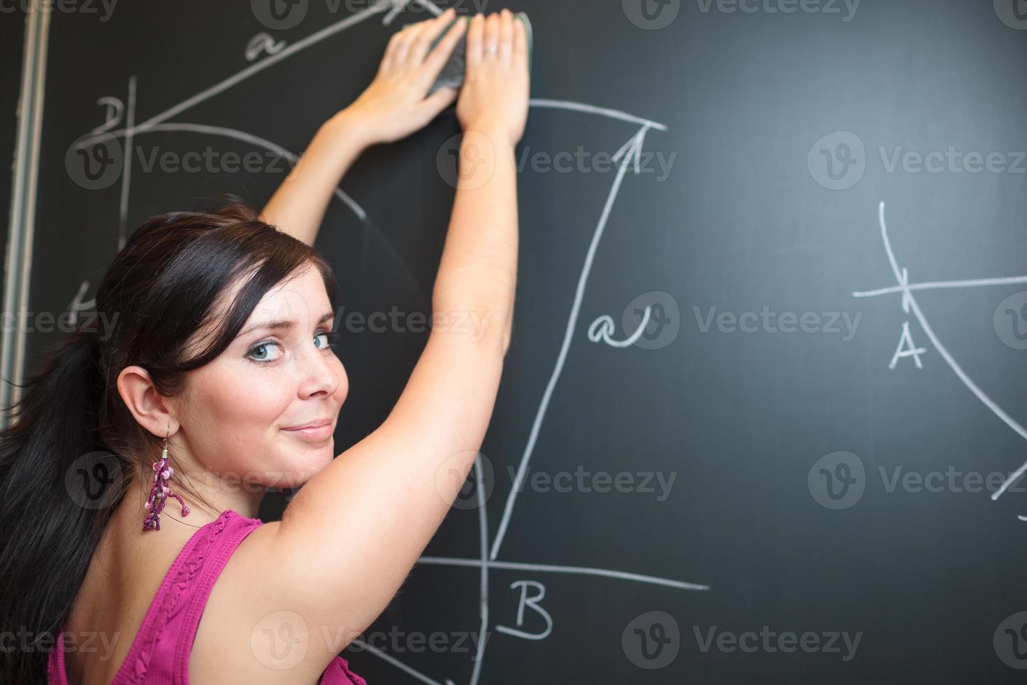 ganska ung lärare som skriver på tavlan foto