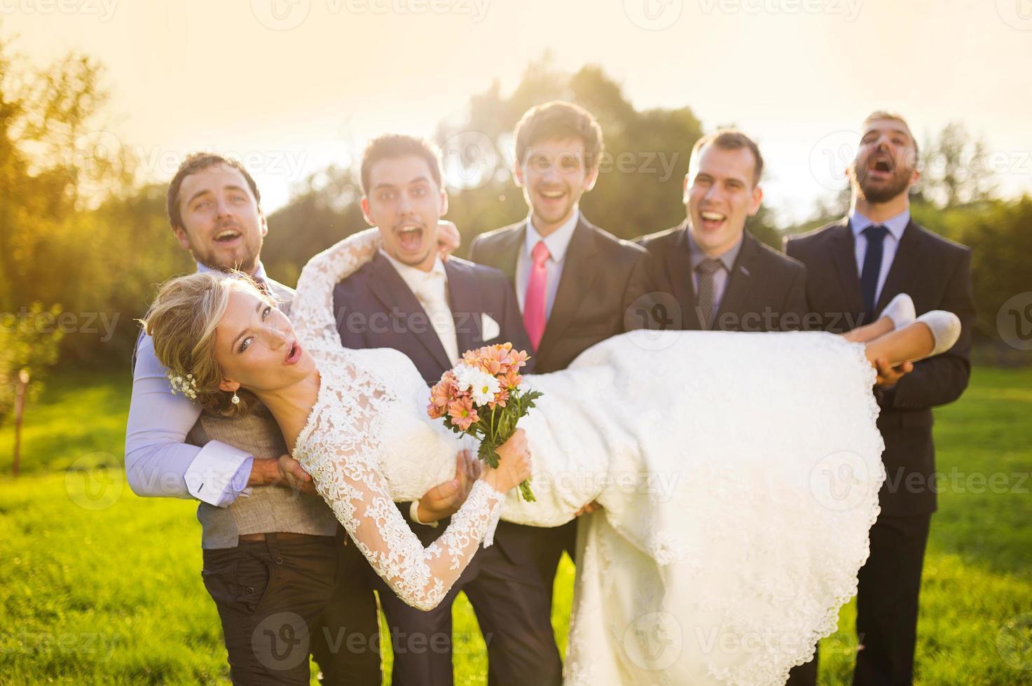 brudgum med sina vänner som håller bruden foto