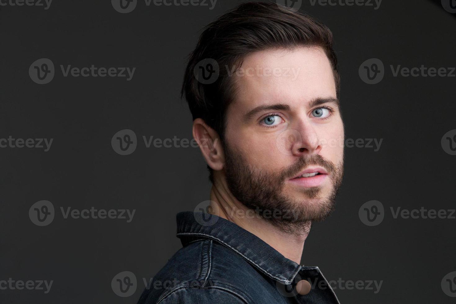 attraktiv ung man som står ensam på grå bakgrund foto
