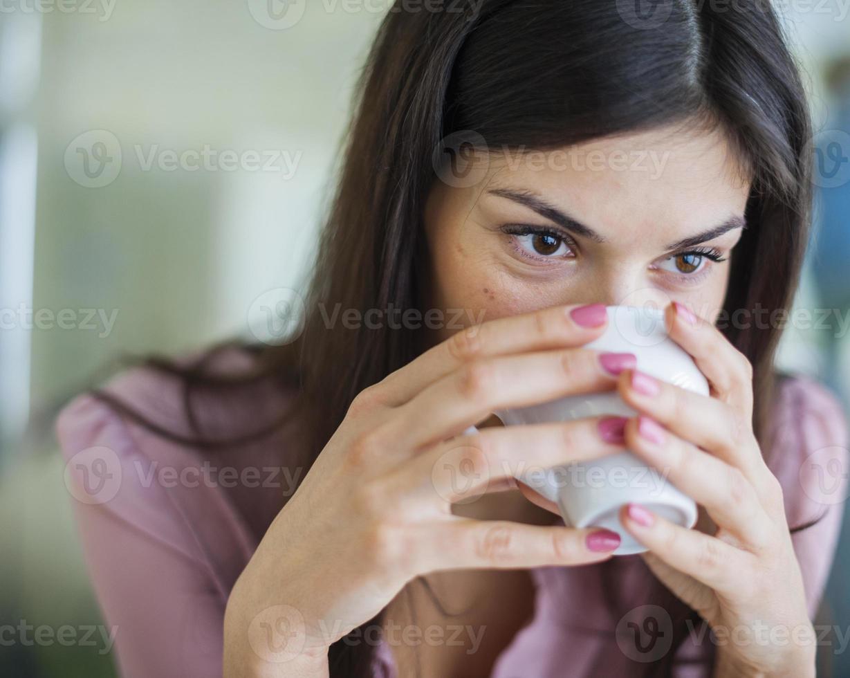 ung affärskvinna som har kaffe på kontoret foto